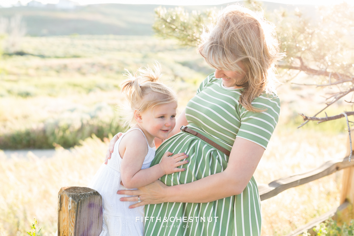 Sister loving on baby bump by Reno maternity photographer