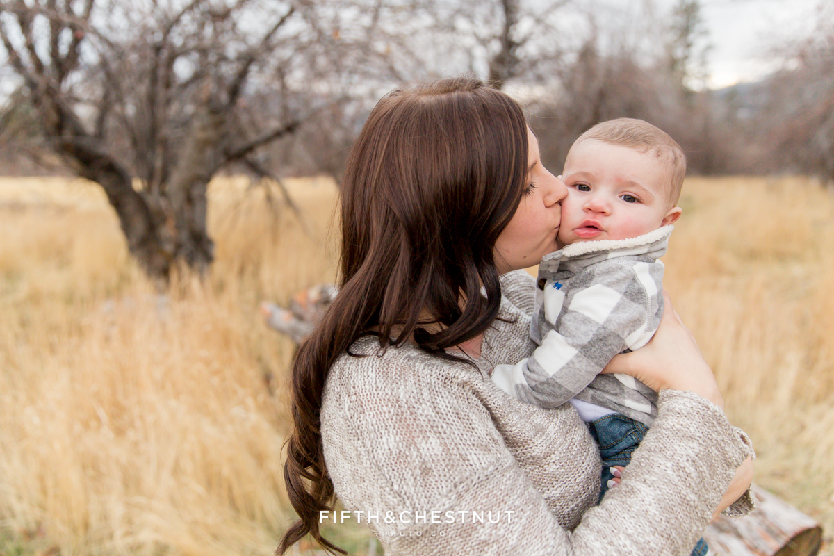 A Mom snuggles and kisses her baby boy for mommy and me photos in Reno by Reno Family Photographer