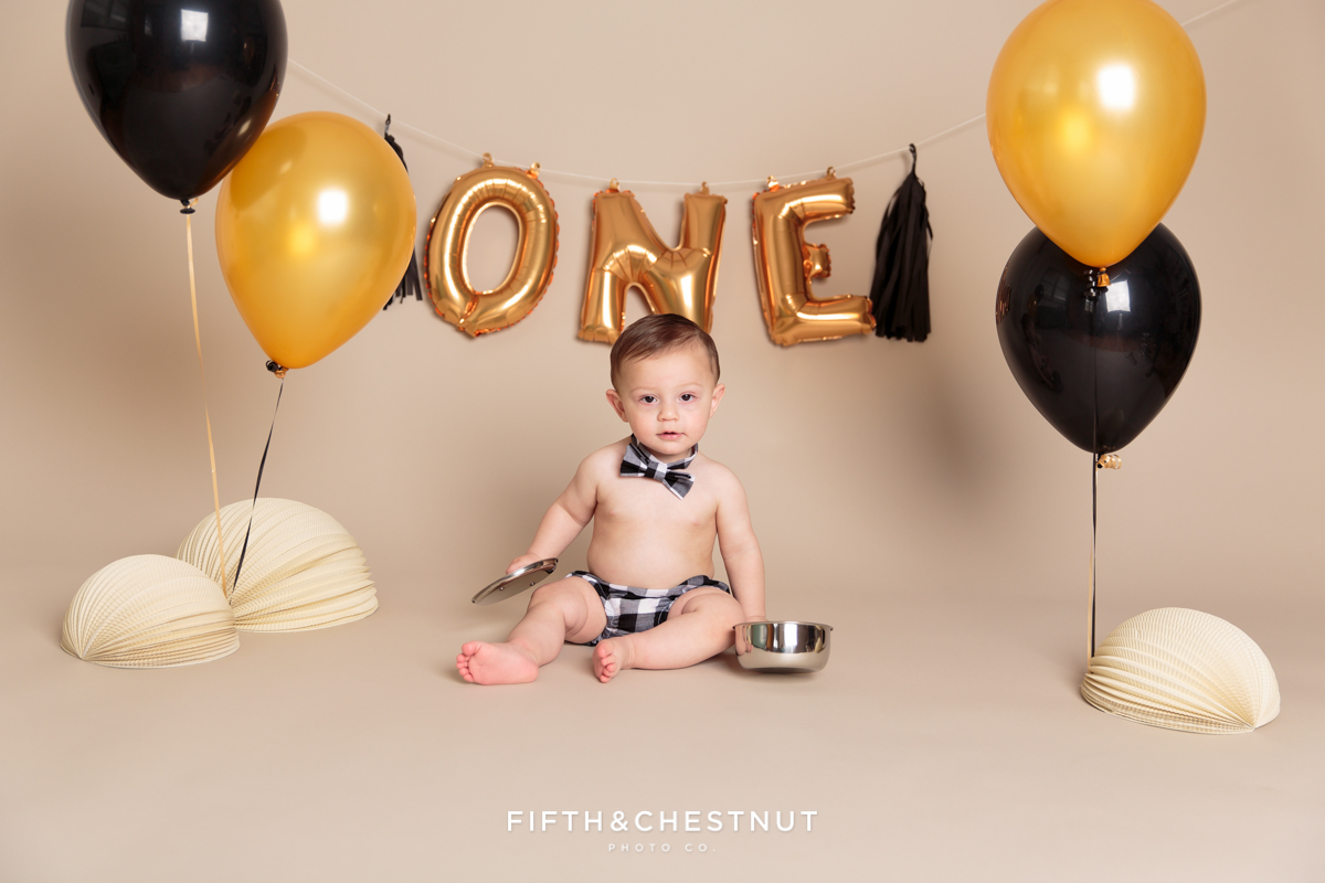 Child posing with pots and pans for his one year spaghetti smash toddler portraits