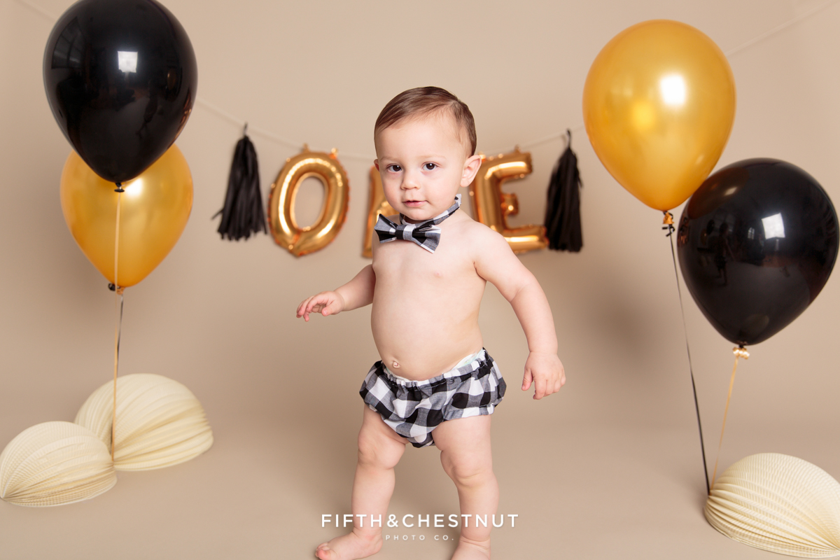 Cute baby boy standing among balloons for his one year spaghetti smash toddler portraits
