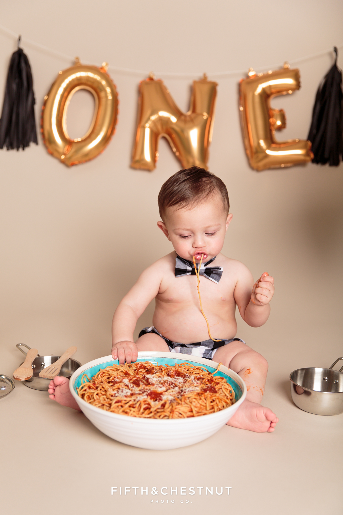 One year old boy digging into giant bowl of spaghetti during one year spaghetti smash toddler portraits