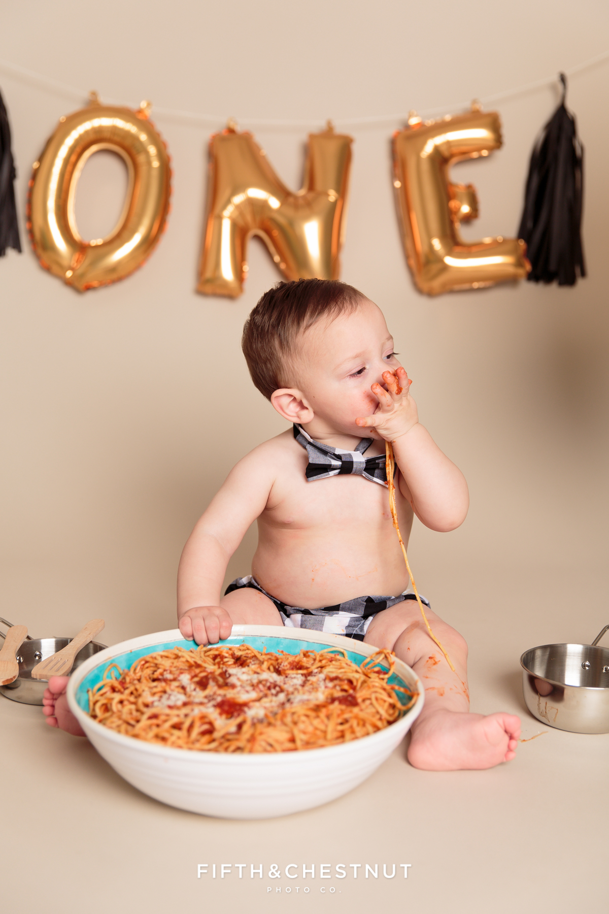 Baby boy wearing a bow-tie and diaper cover eating spaghetti