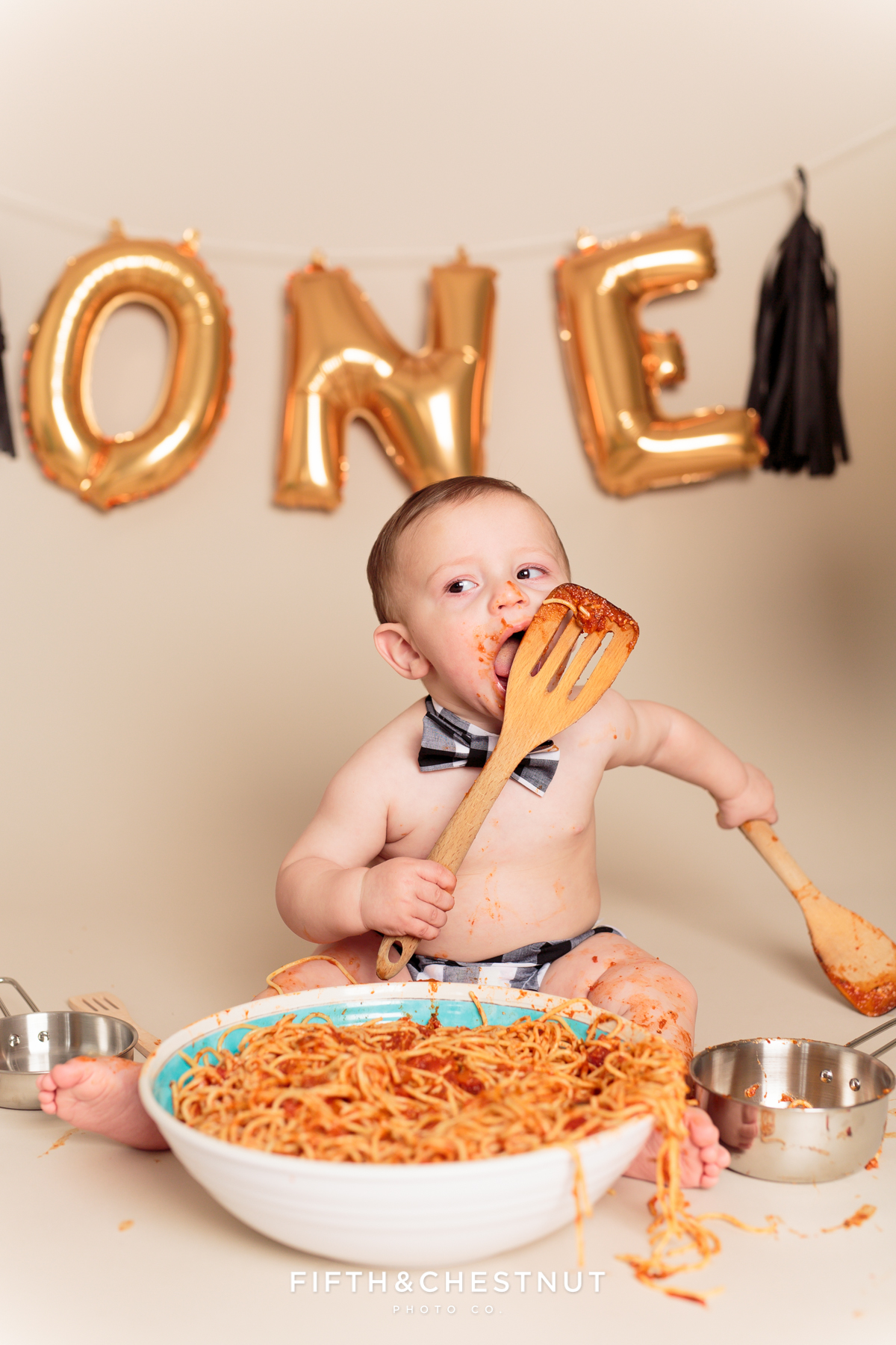 toddler licking spoon of spaghetti
