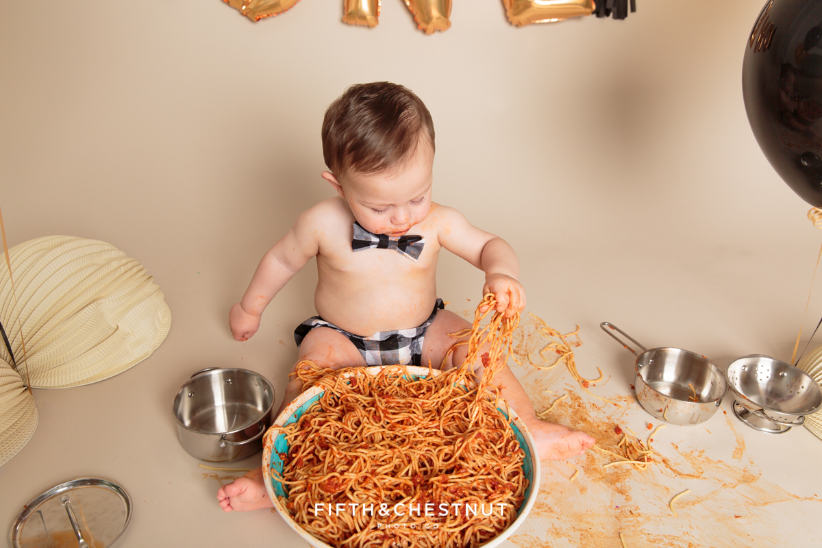 portrait of boy eating spaghetti by reno baby photographer