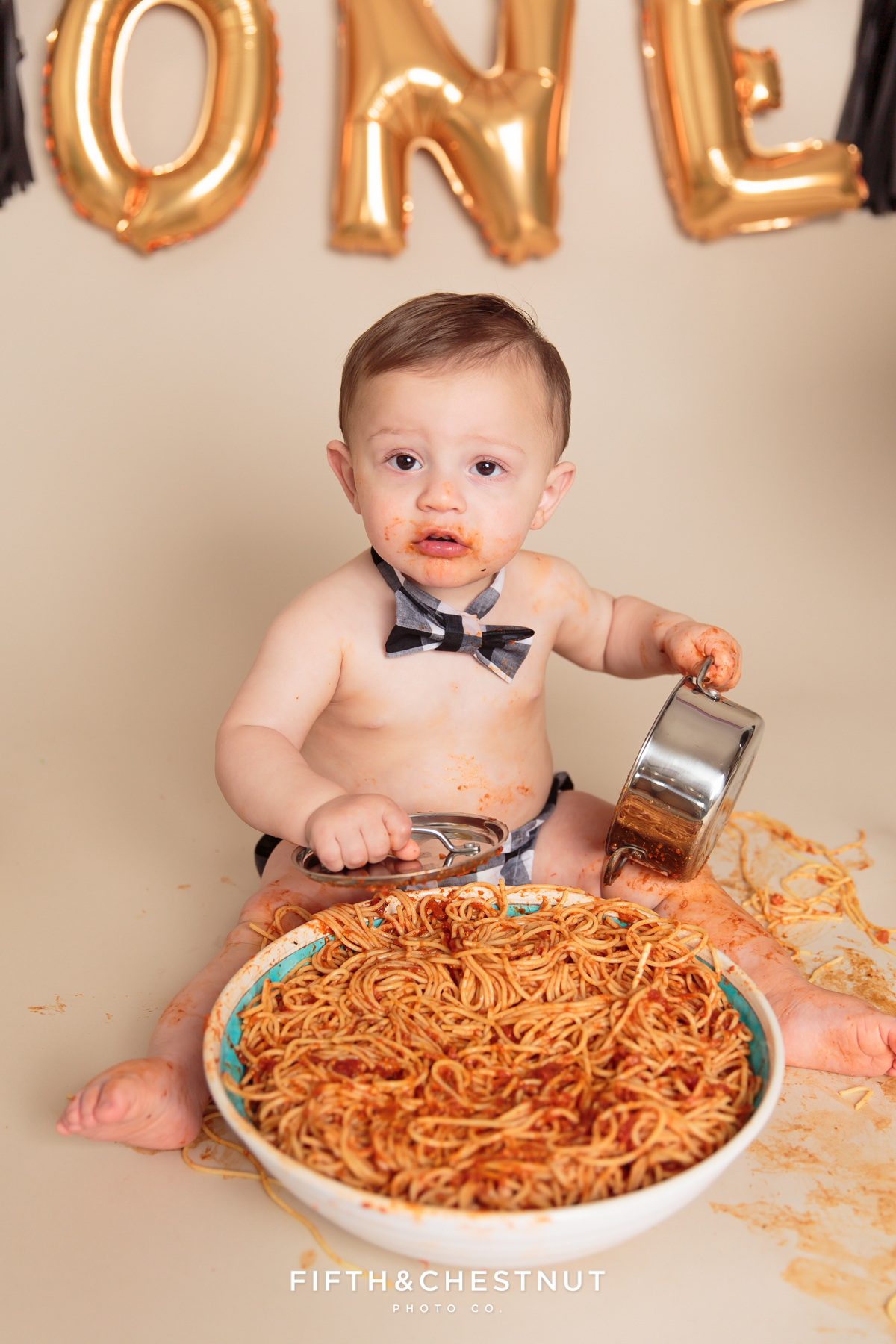 toddler chowing down on spaghetti during his one year spaghetti smash toddler portraits