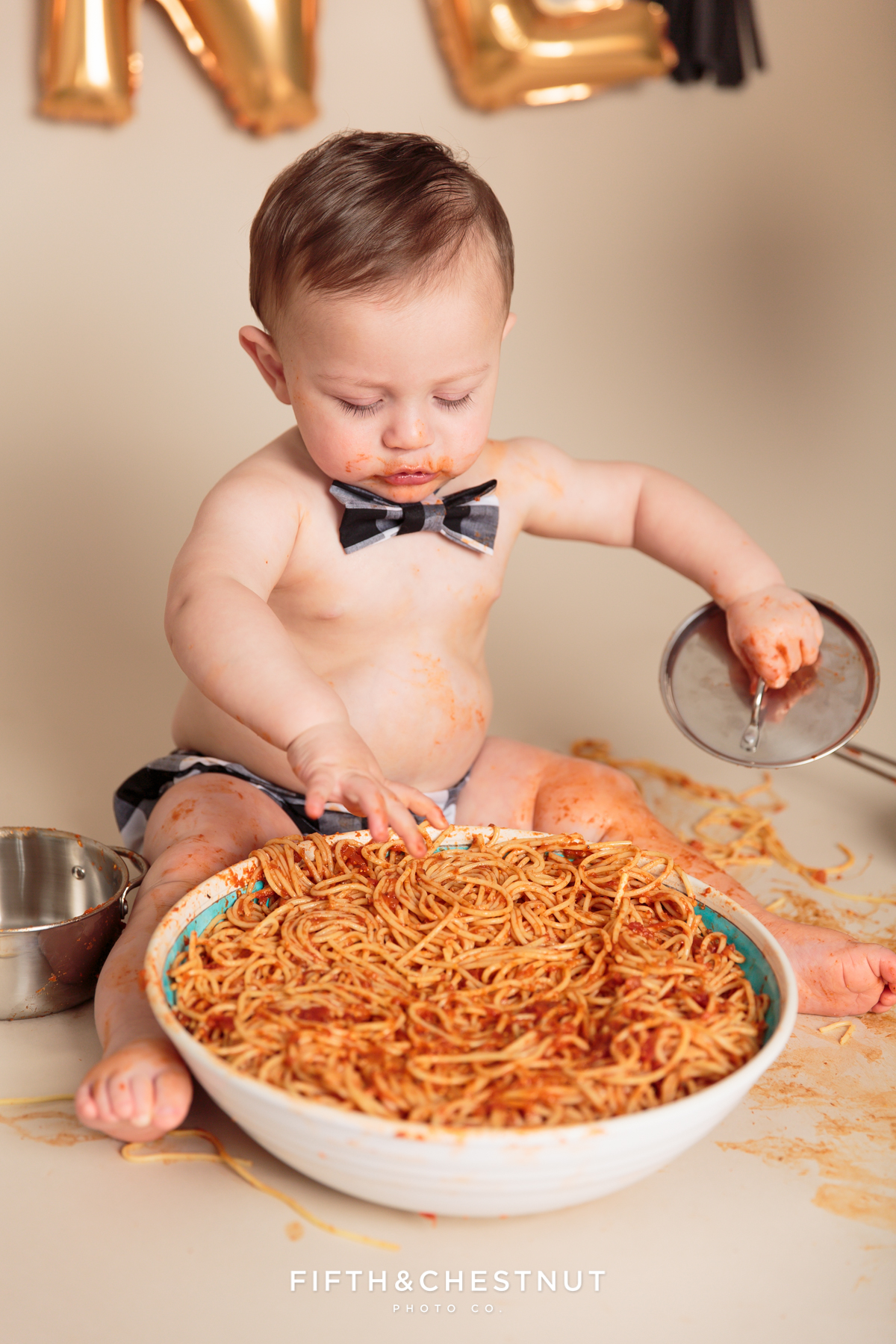 toddler using pots and pans during his one year spaghetti smash toddler portraits