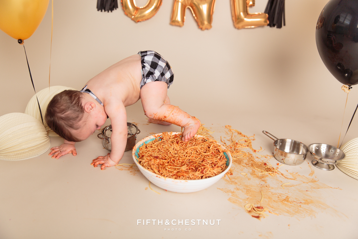 baby boy stepping into his giant spaghetti bowl after his one year spaghetti smash toddler portraits
