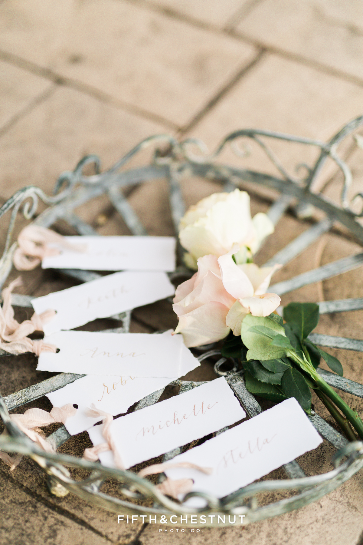 Escort cards on a vintage tray with roses for a Dusty Blue Private Estate Country French Wedding Styled Shoot