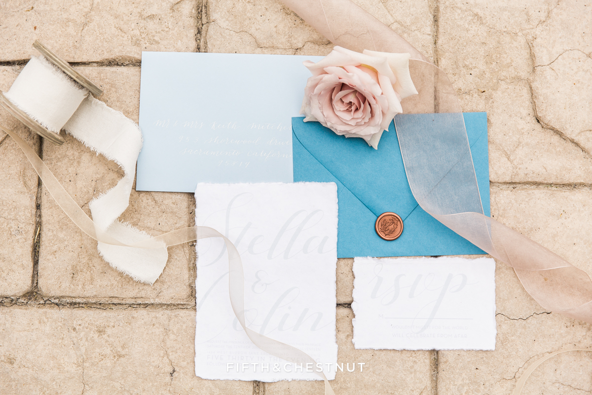romantic wedding invitation suite and flowers and ribbon for a Dusty Blue Private Estate Country French Wedding Styled Shoot
