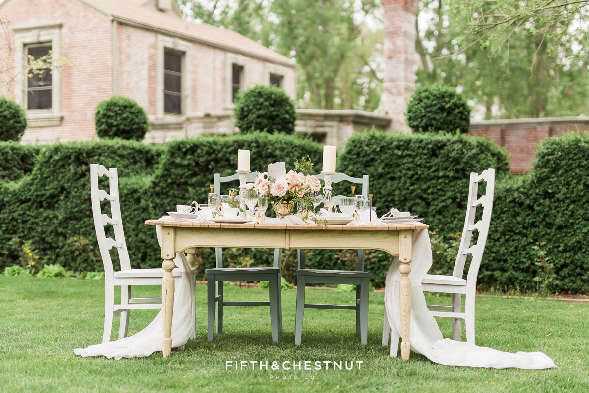 Table setting in front of a private estate for a dusty blue country french wedding styled shoot