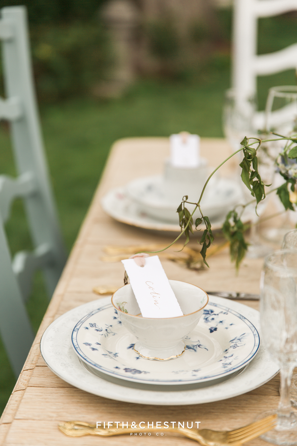 tea cups and plates with gold flatware on vintage dining table for a Dusty Blue Private Estate Country French Wedding Styled Shoot