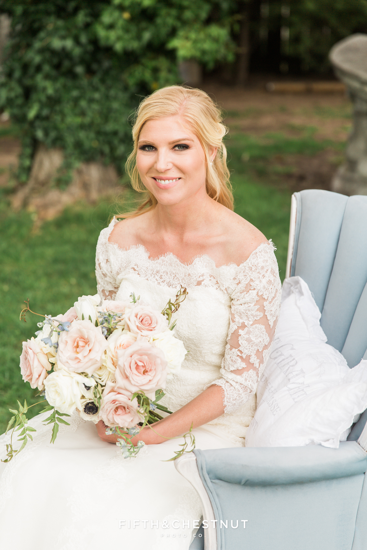 A gorgeous blonde bride smiles at the camera holding a whimsical wedding bouquet on a country french blue chair at a private estate
