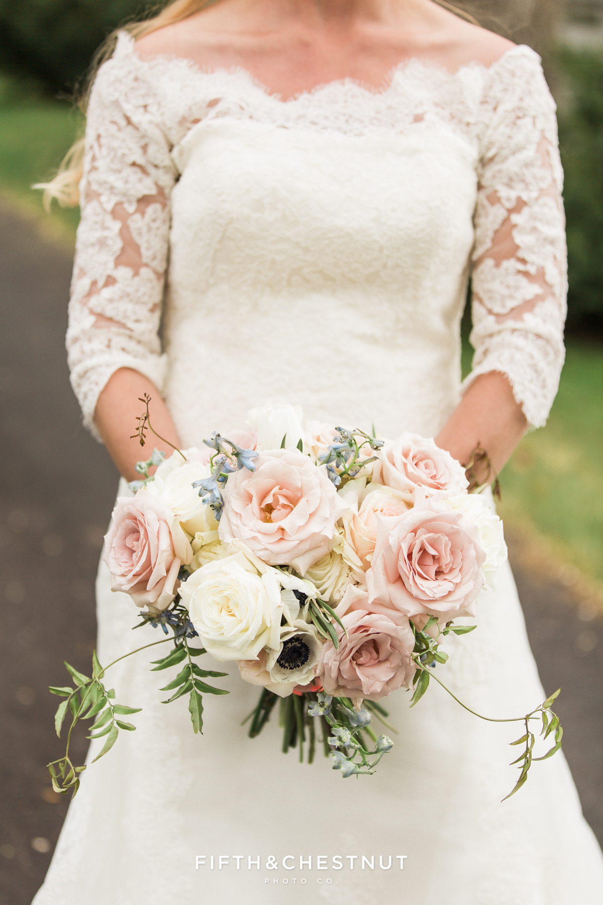 Bride in a lace wedding dress showing off her country french bouquet for a dusty blue wedding styled shoot