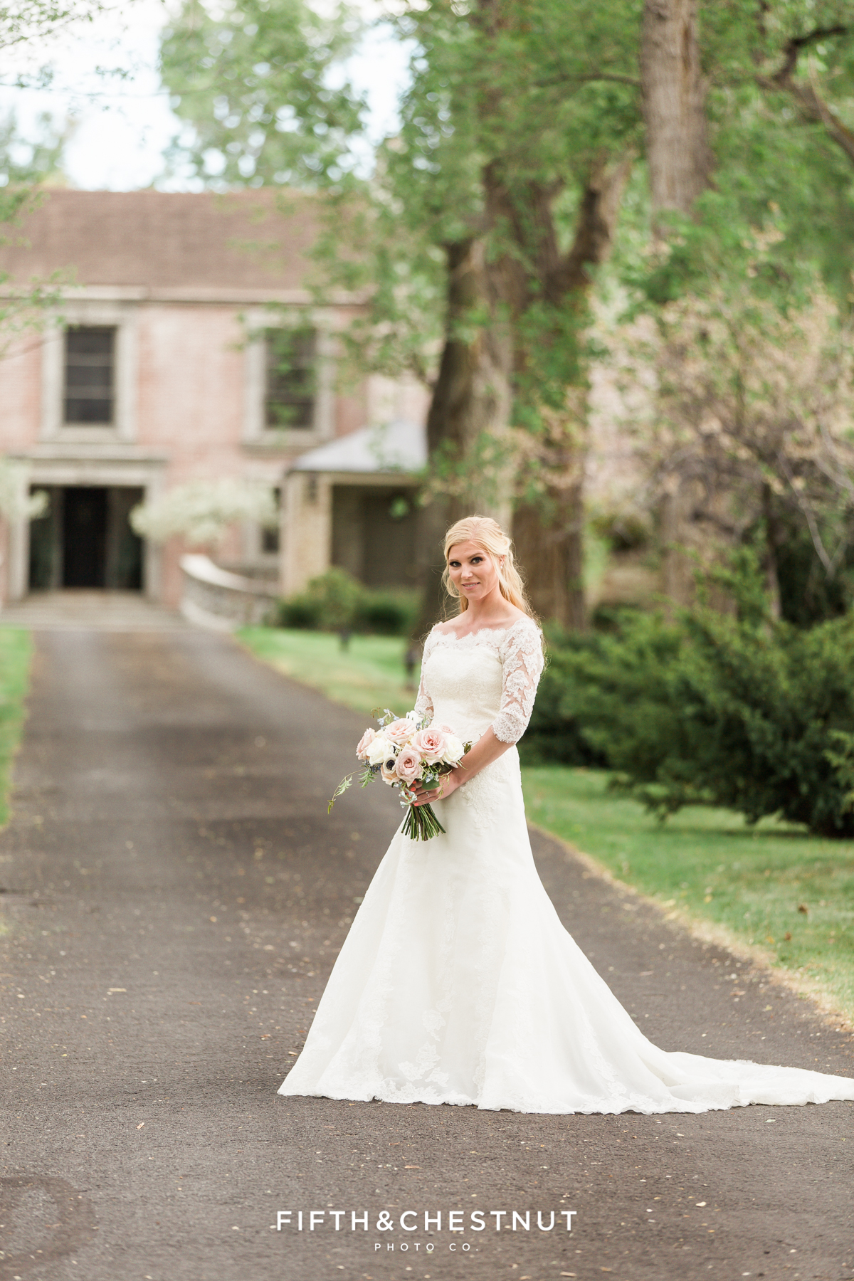 Happy bride in lace dress standing in an oak-lined pathway leading to a stone and brick private estate