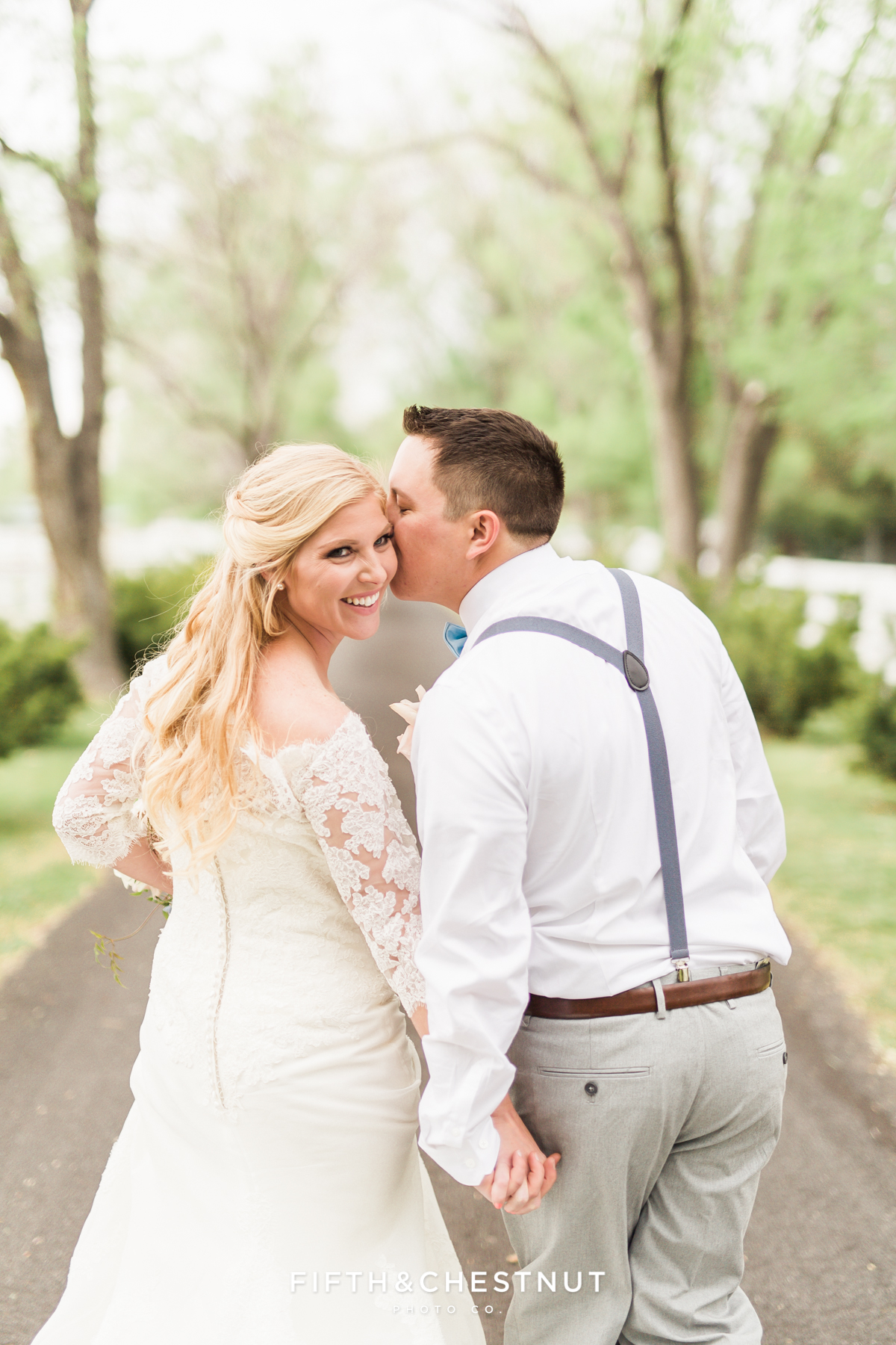 Bride laughing as her groom kisses her cheek as they walk down an oak-lined path