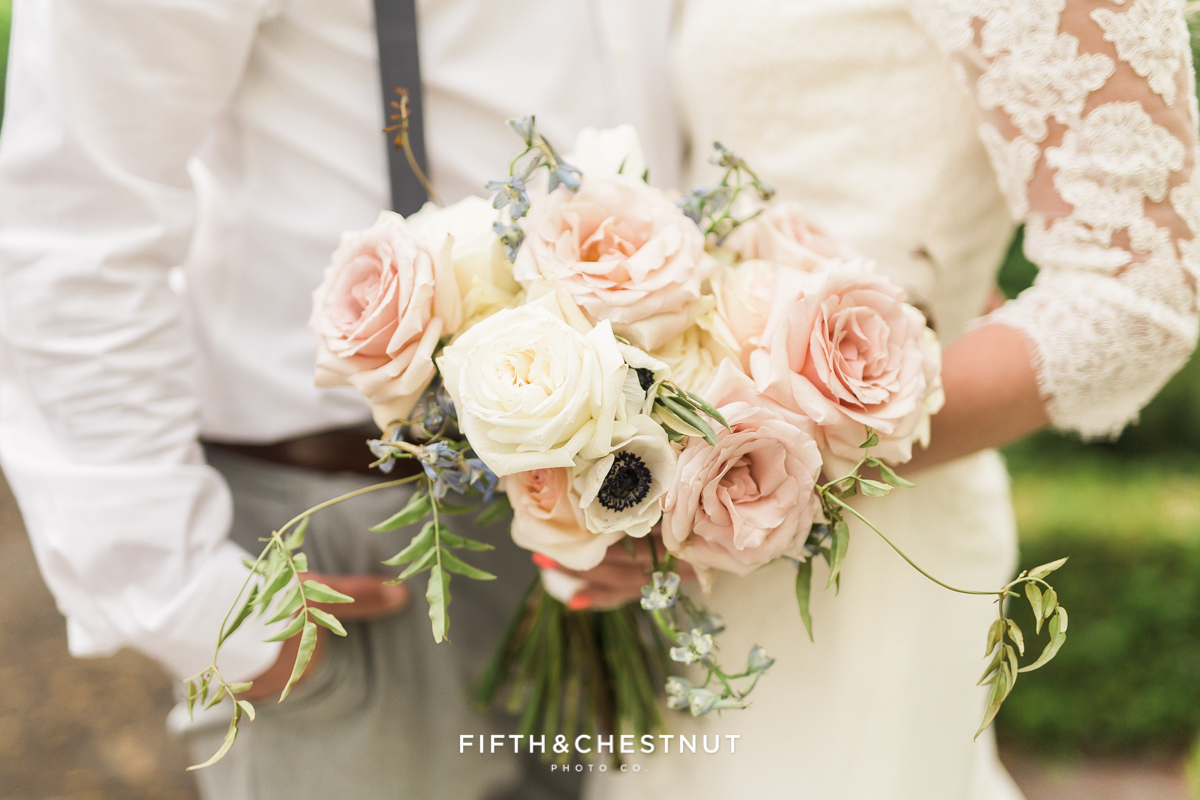 Closeup of country french wedding bouquet as bride stands close to groom