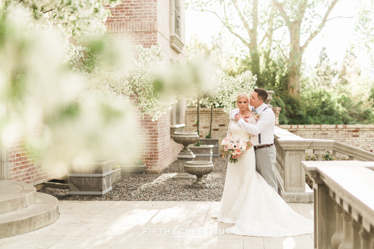 Bride and groom embrace on the blossom-lined front porch of a Reno brick and stone private estate