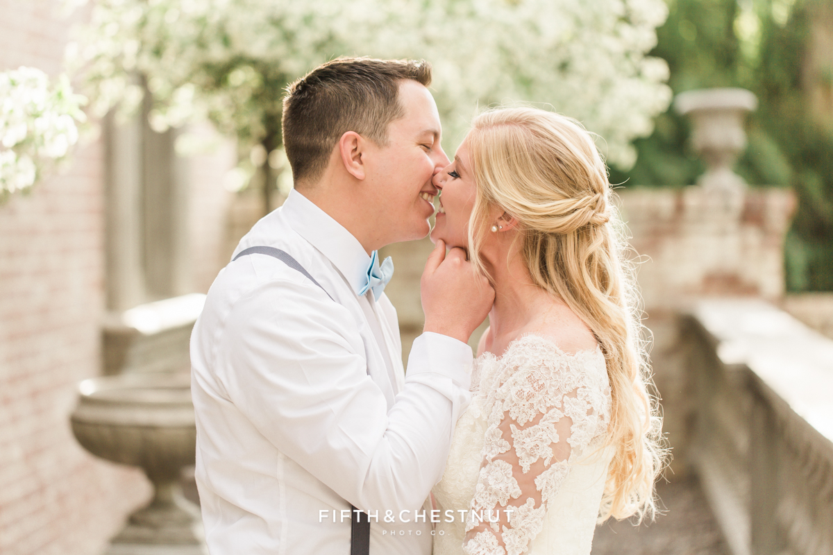 Bride and groom share a sweet kiss on a blossom-lined front porch of a brick private estate