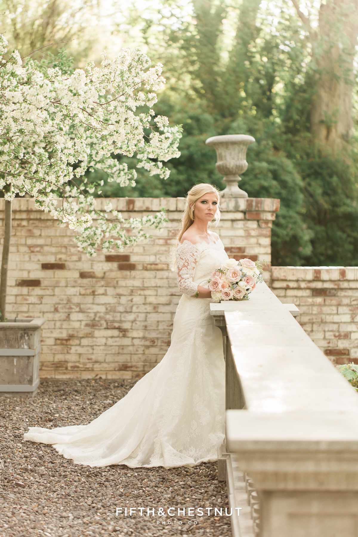 A bride stands on the front porch of a private estate for her country french inspired wedding
