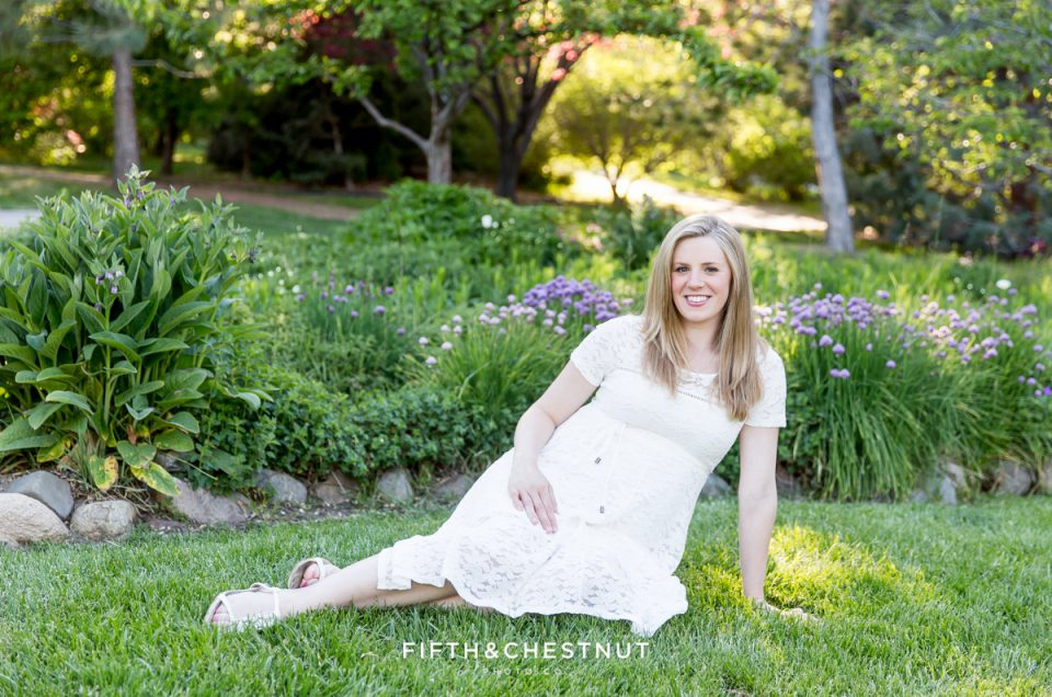 Spring Reno Maternity Portrait of woman sitting in front of purple flowers by Reno Maternity Photographer