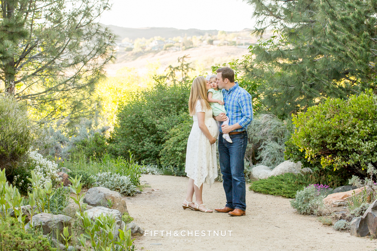 Mom and dad kiss their daughter's cheeks while standing in a path lined with flowers and plants at Rancho San Rafael park in reno
