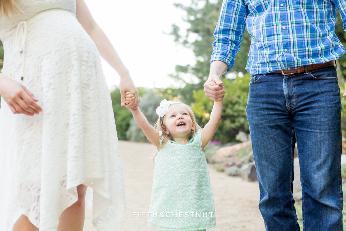 Portrait of happy smiling toddler in between her mom and dad while they hold hands