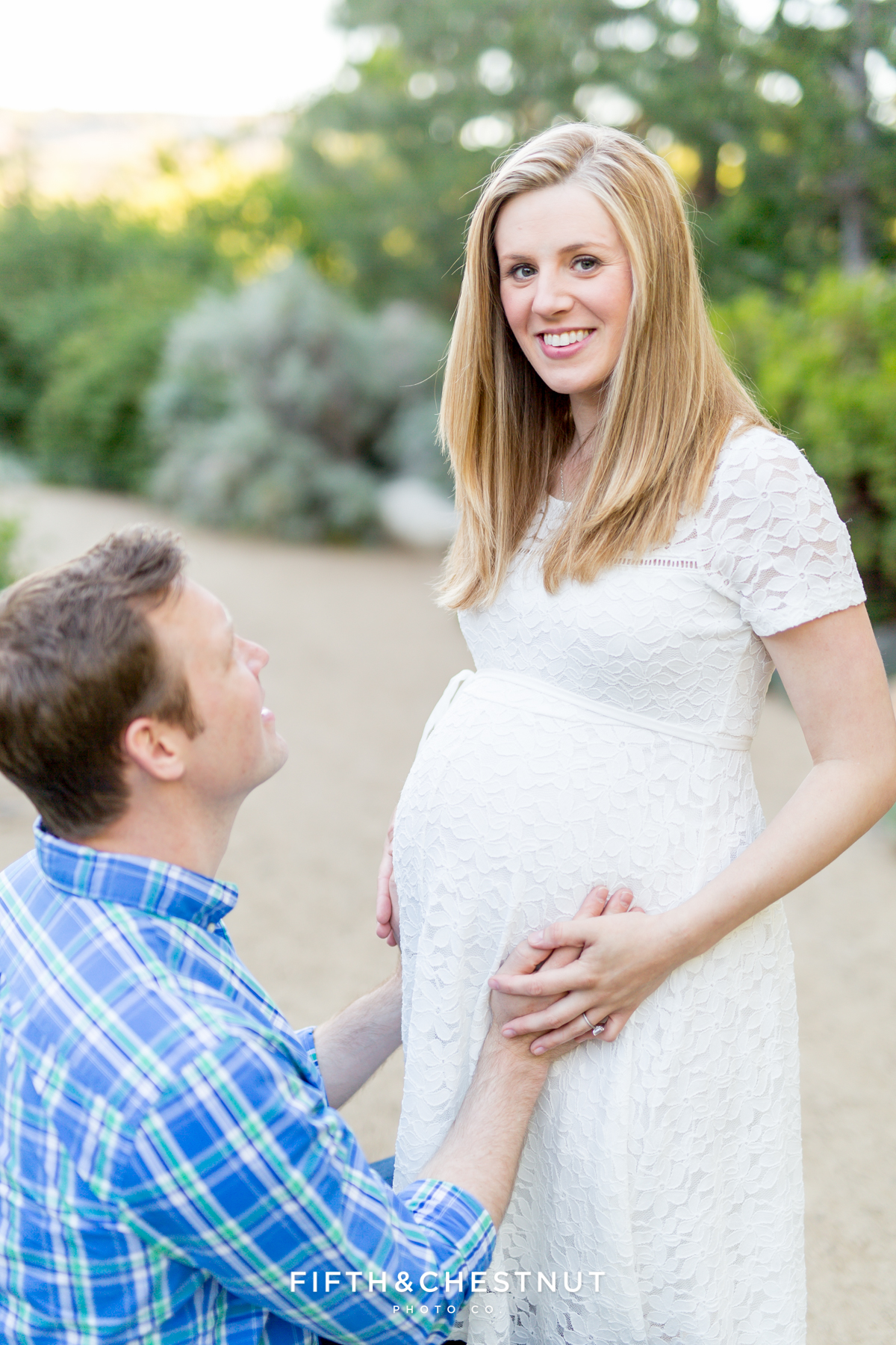 a husband and pregnant wife smile at the camera for a lovely sprintime maternity portrait in Reno