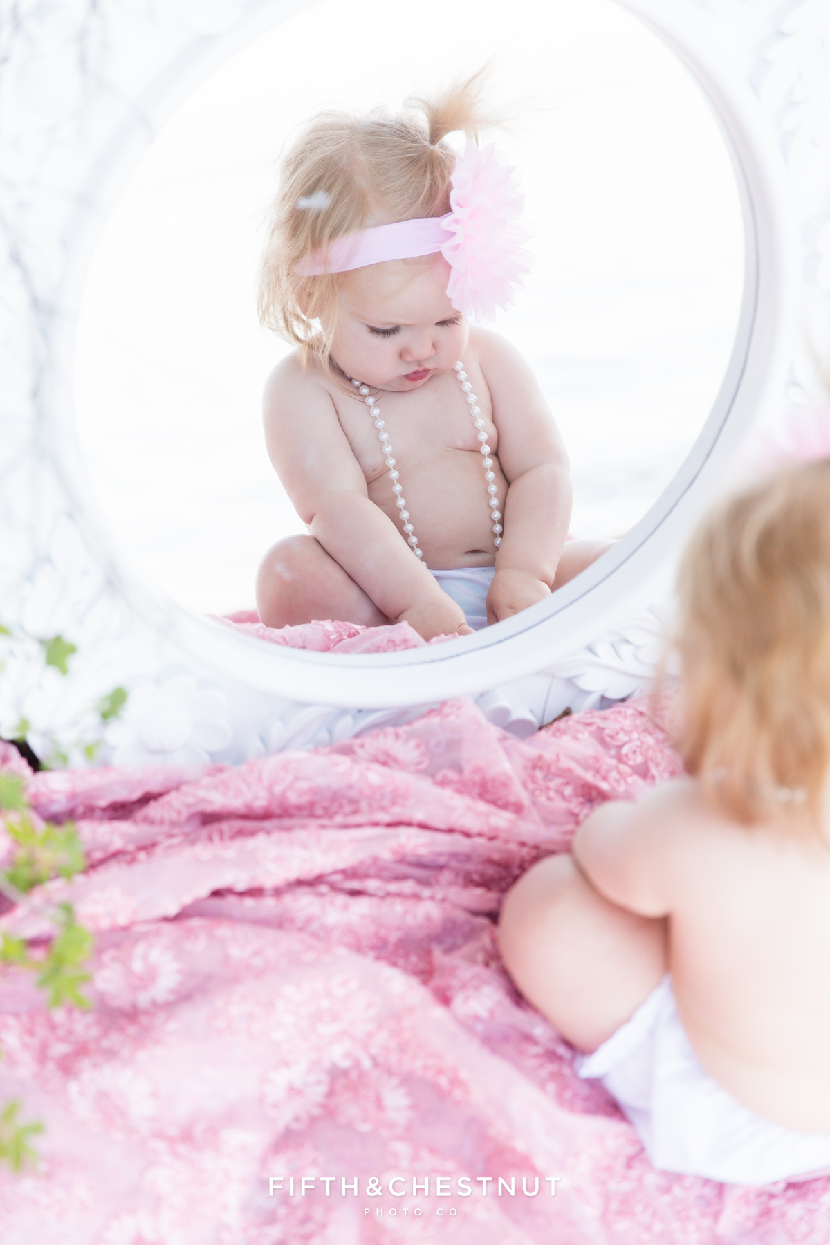 One year old girl playing with pearls and looking into mirror on Kiva Beach in Lake Tahoe