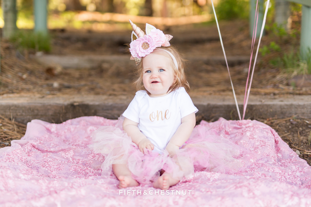 "One year old girl sitting on floral pink blanket wearing a ""One"" onsie and unicorn headband for photos by Reno Baby Photographer at Kiva Beach Lake Tahoe"
