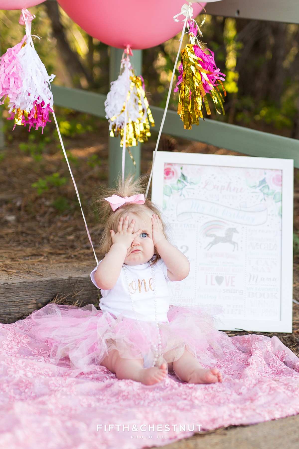One year photos of baby girl making silly face at Kiva Beach with pink balloons and sign