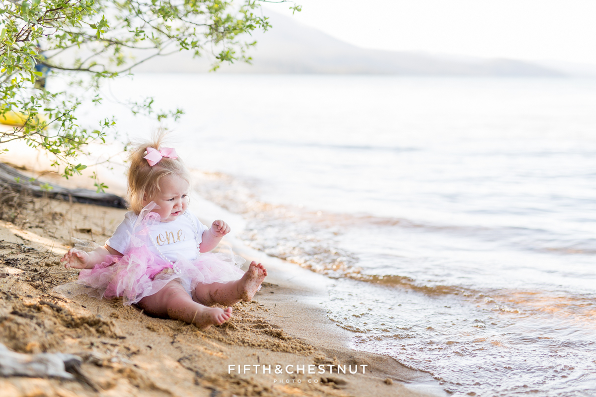 One year photos of little girl on sandy beach getting her feet wet from the waves