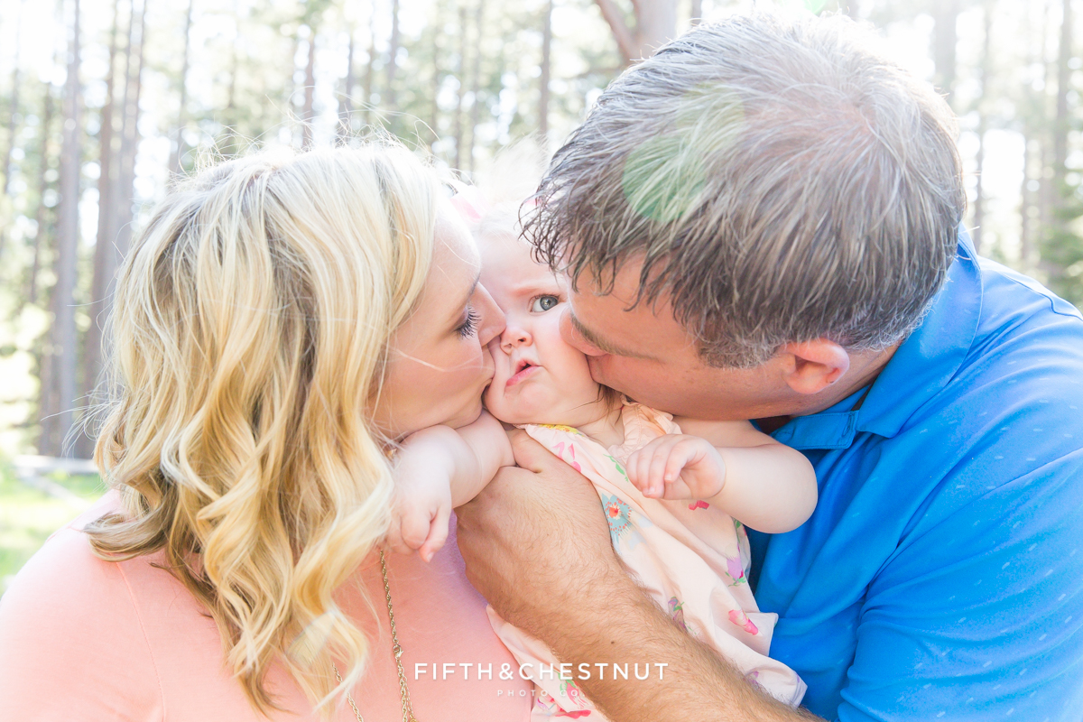 Mom and Dad kissing their one year old baby girl in Kiva Beach, Lake Tahoe for a family photoshoot by Lake Tahoe Family Photographer