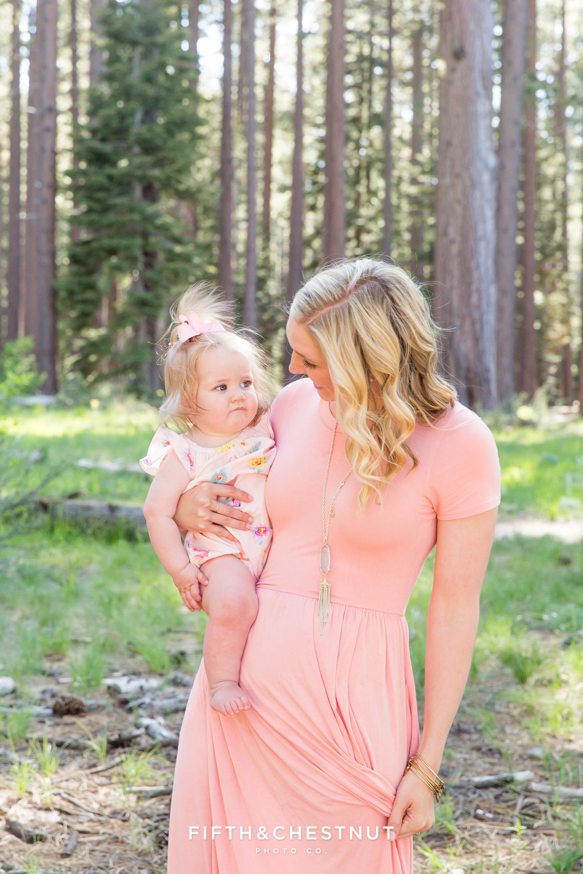 Portrait of a mom and her one year old daughter at Kiva Beach in the wooded area in Spring by Lake Tahoe Family Photographer
