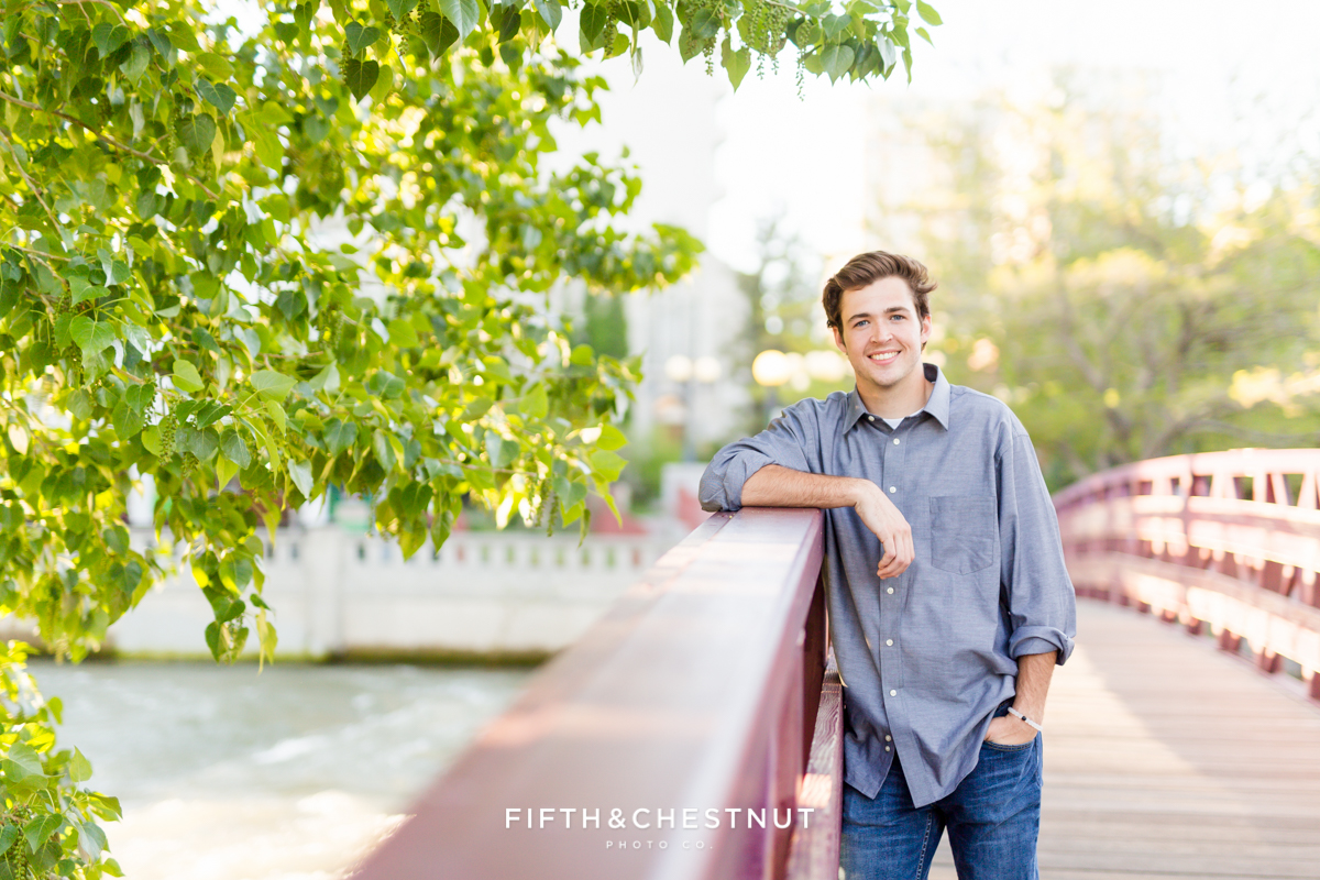 Reno High School Senior leans on bridge at Wingfield Park for his Reno Senior Portraits by Reno Senior Photographer