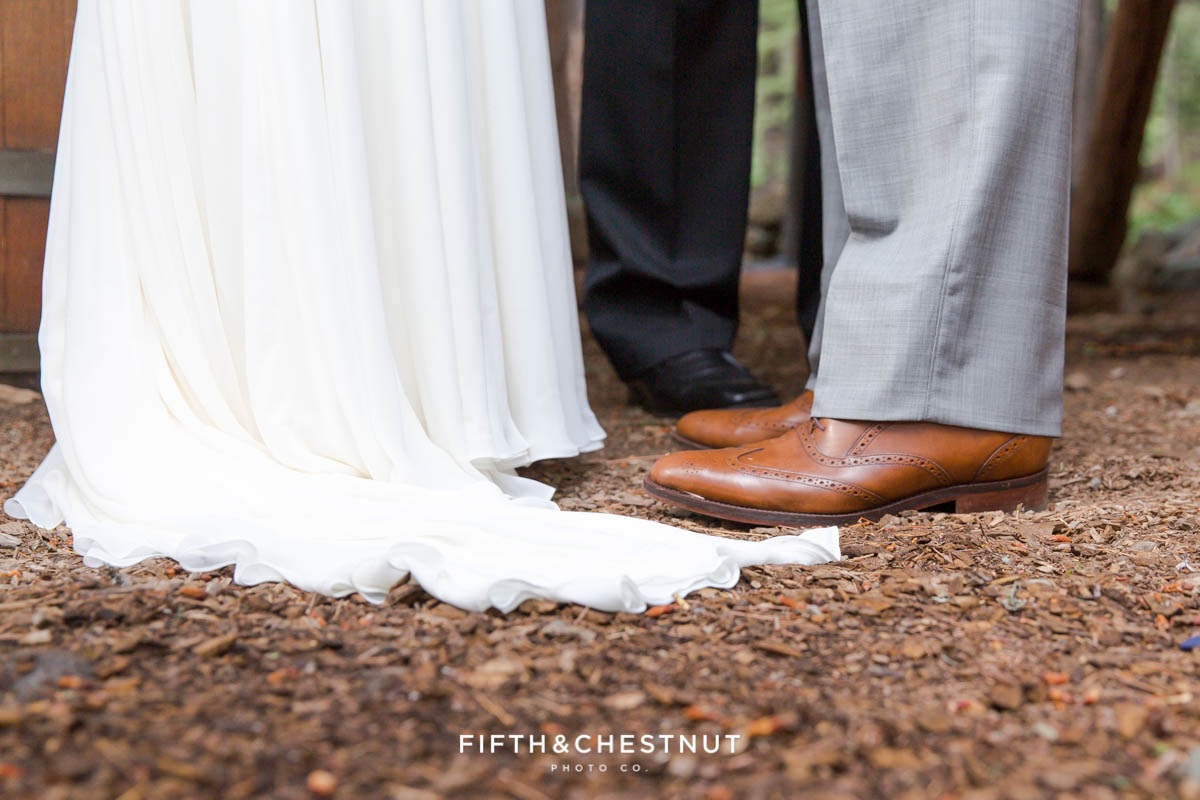 Detail photo of bride's dress and groom's brown leather shoes