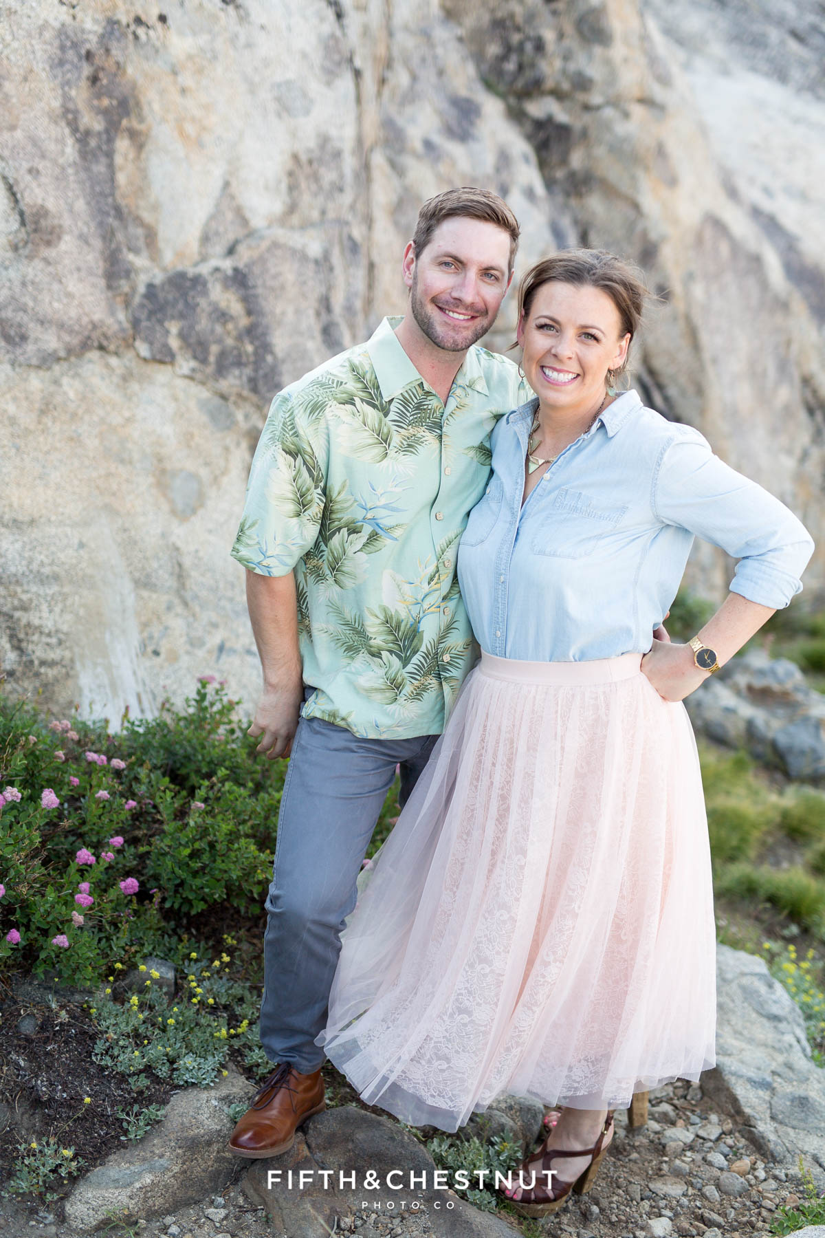 couple smiles while standing in front of boulders and wildflowers at the Donner Summit Bridge lookout for their donner lake engagement with Quincy Wedding Photographer