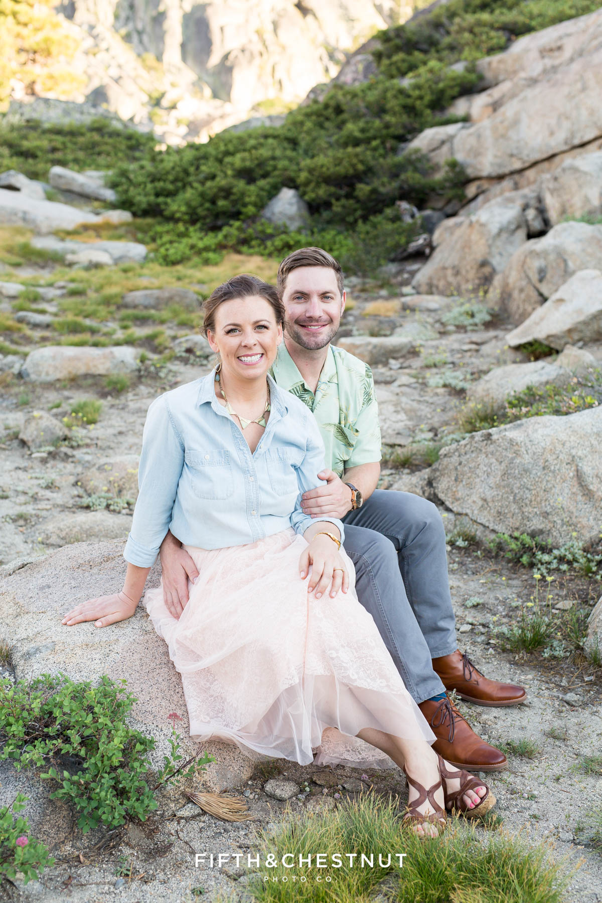 couple sitting on granite boulders at the Donner Summit Bridge turnout for portraits by Quincy Wedding Photographer