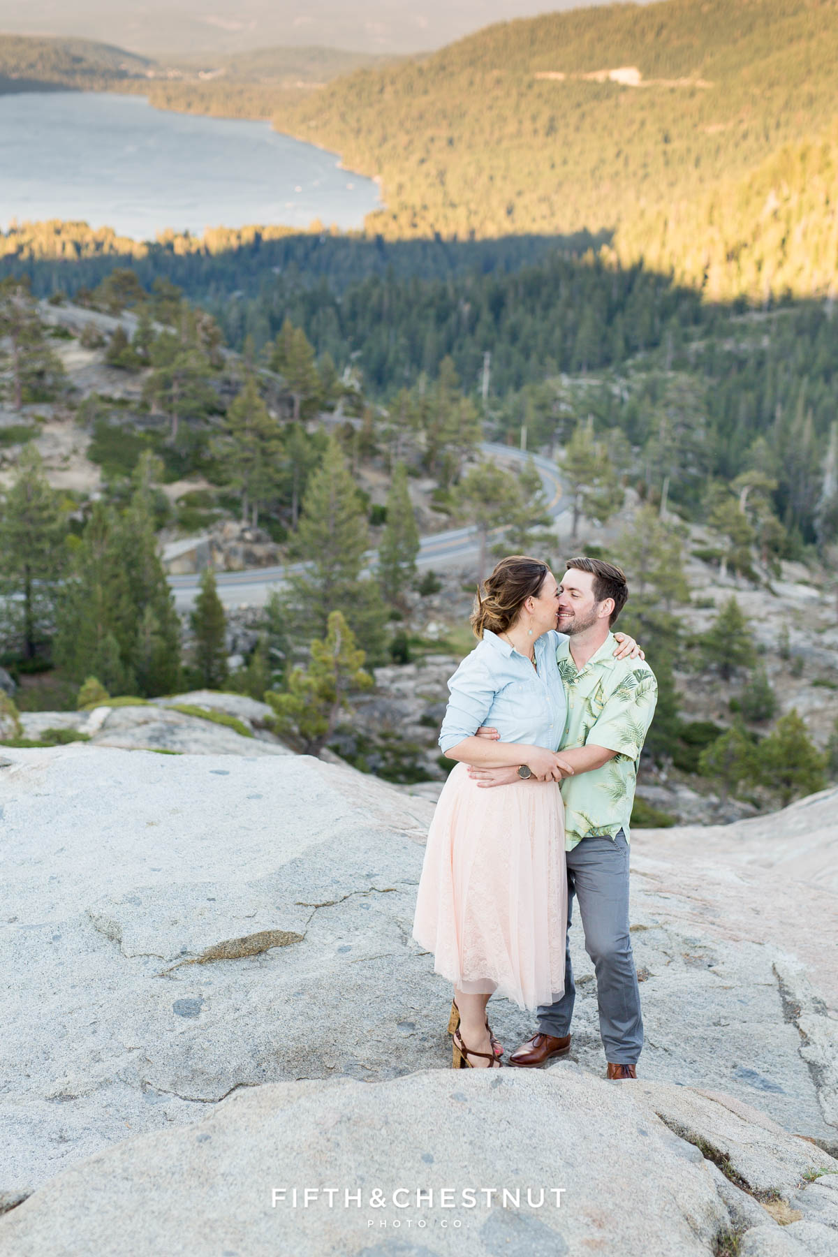 Engaged couple embrace above Donner Lake on granite rocks while wearing pastel colors for their Donner Lake Engagement session