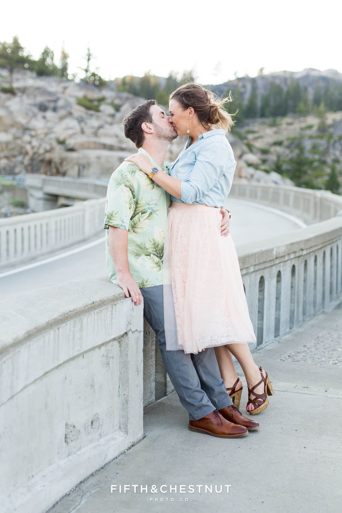 Engaged couple kisses on the Donner Summit Bridge for engagement portraits by Quincy Wedding Photographer