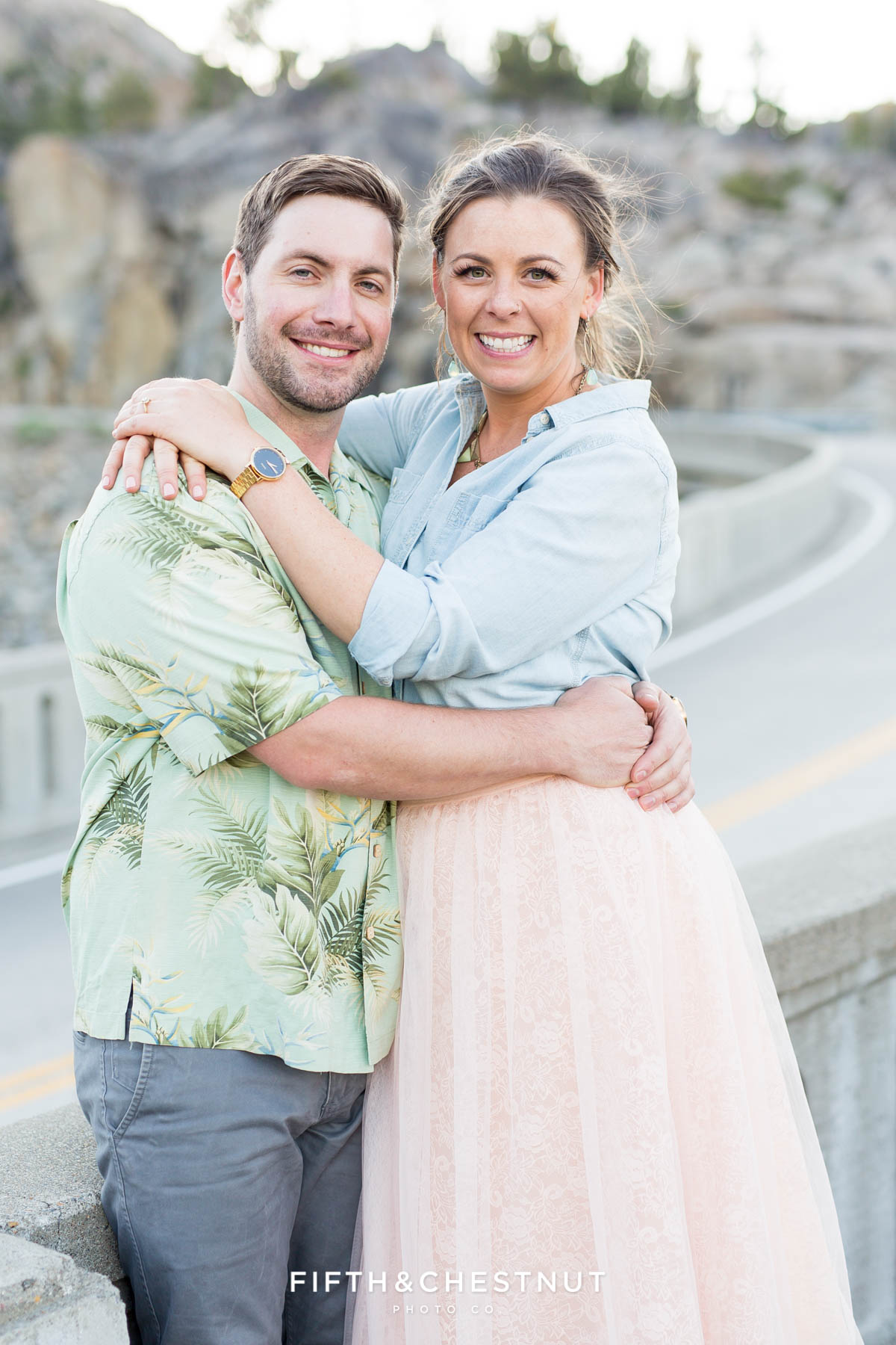 Bride and groom smile while standing in front of the Donner Summit Bridge in Truckee, CA