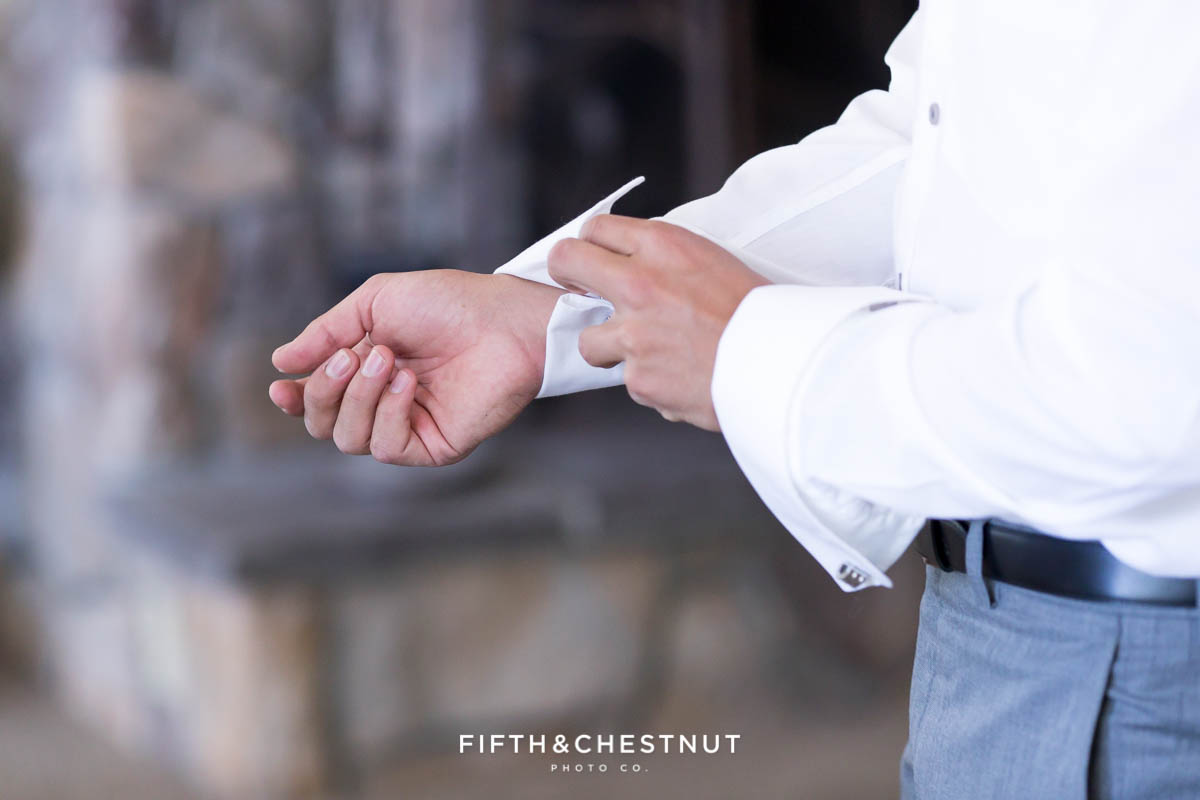Groom buttons up shirt before his North Lake Tahoe Wedding by Lake Tahoe Wedding Photographer