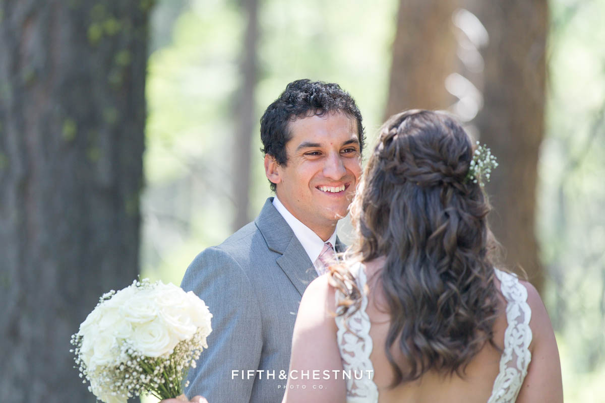Groom sees his bride for the first time on their wedding day and smiles wildly at her