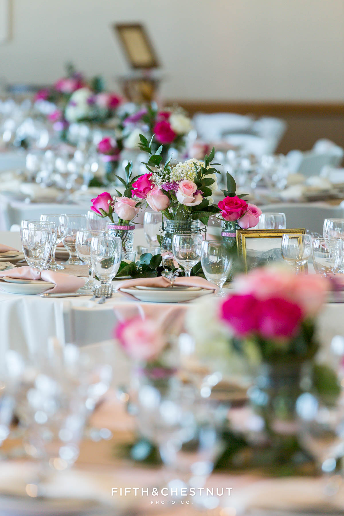 Wedding reception tables with vases of roses and place settings for a North Lake Tahoe Wedding