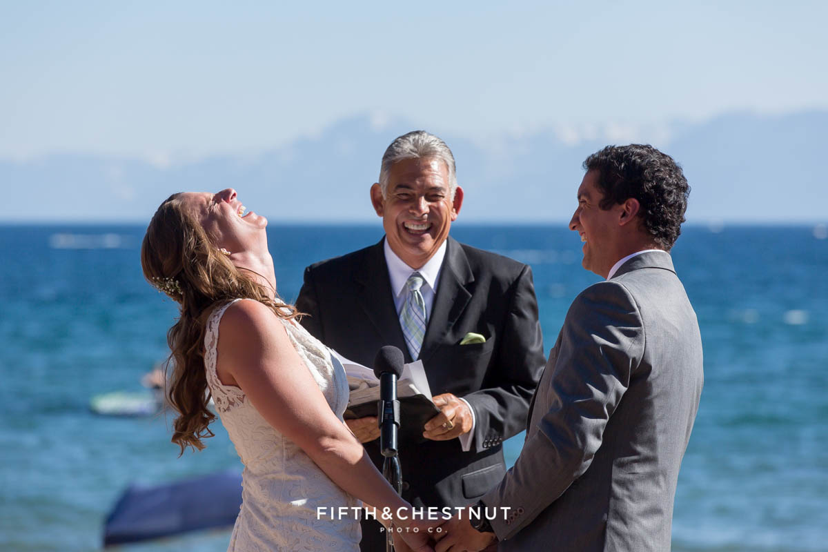 Bride and groom laugh hysterically during wedding ceremony on the beach of lake tahoe