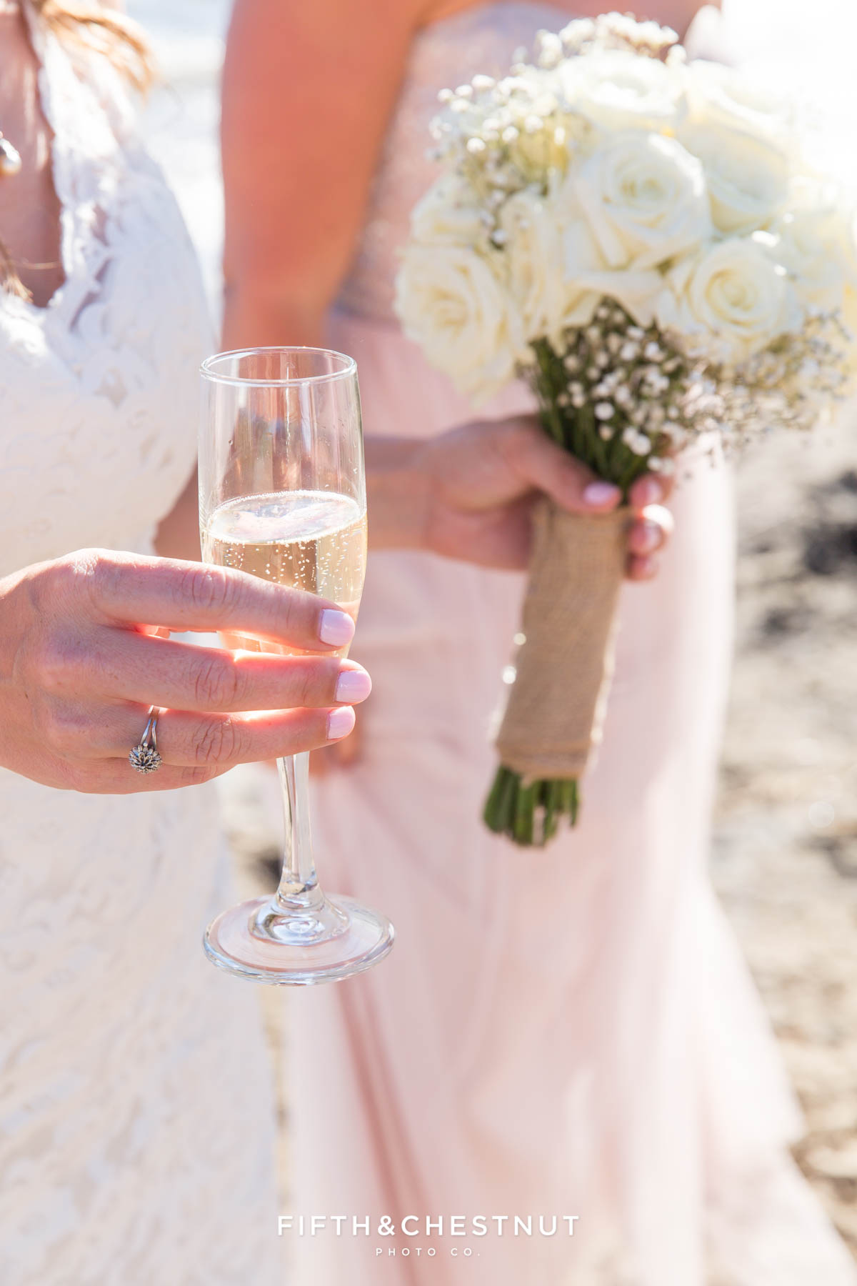 Bride holding bouquet and a glass of sweet champagne on the beach of North Lake Tahoe