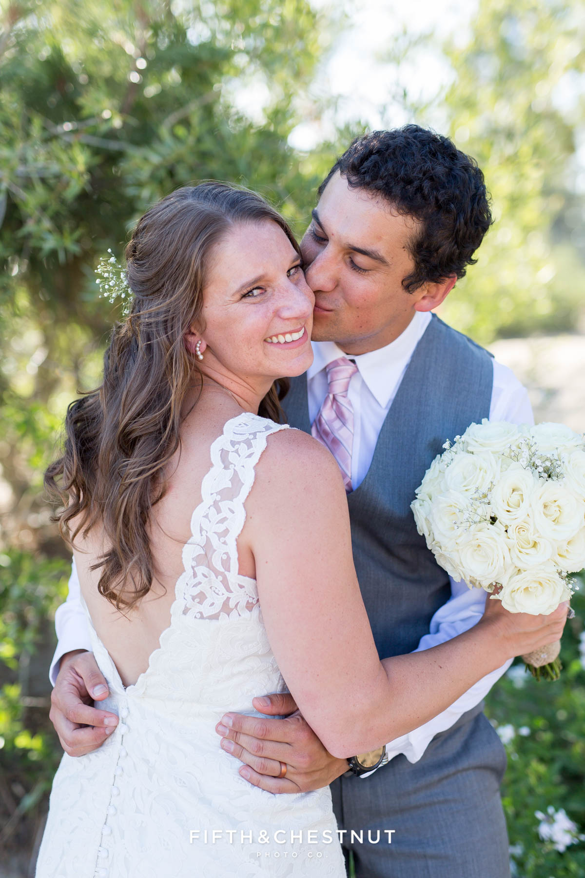 Groom kisses his bride on the cheek as she looks at the camera for their North Lake Tahoe Wedding by Tahoe Photographer