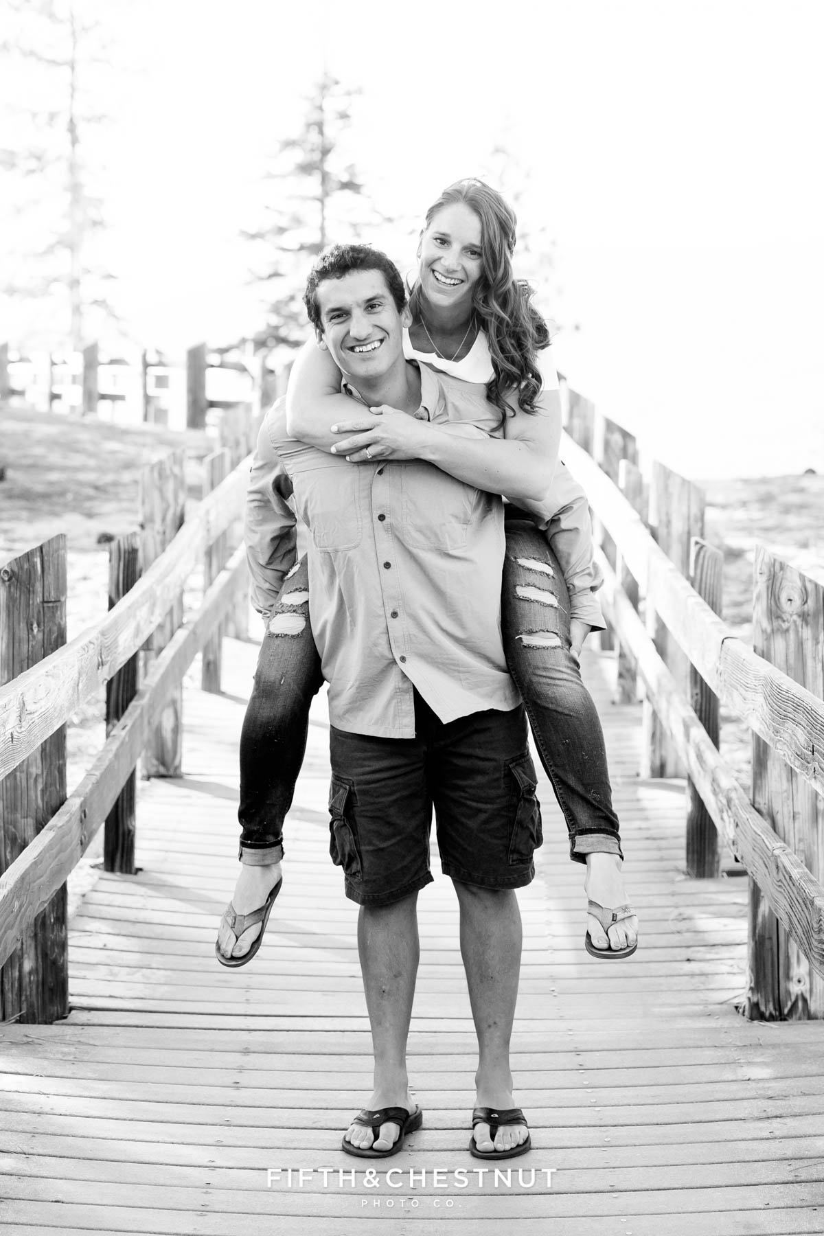 bride-to-be riding piggyback on her groom-to-be at Sand Harbor for their casual summer Tahoe engagement