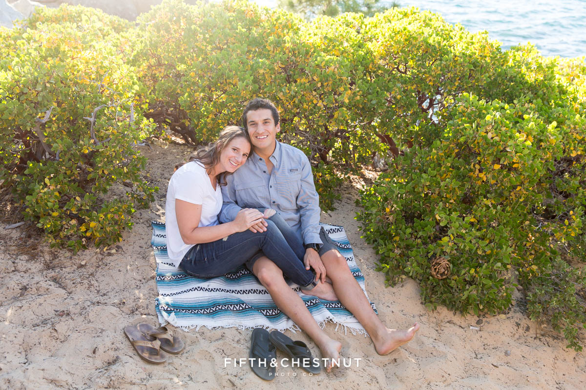 couple snuggles together on south american style blanket for their summer Tahoe engagement