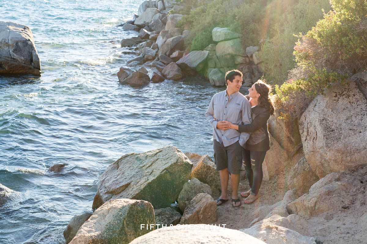 Bride and groom stand together between rocks overlooking Lake Tahoe for their engagement photos by Lake Tahoe wedding photographer