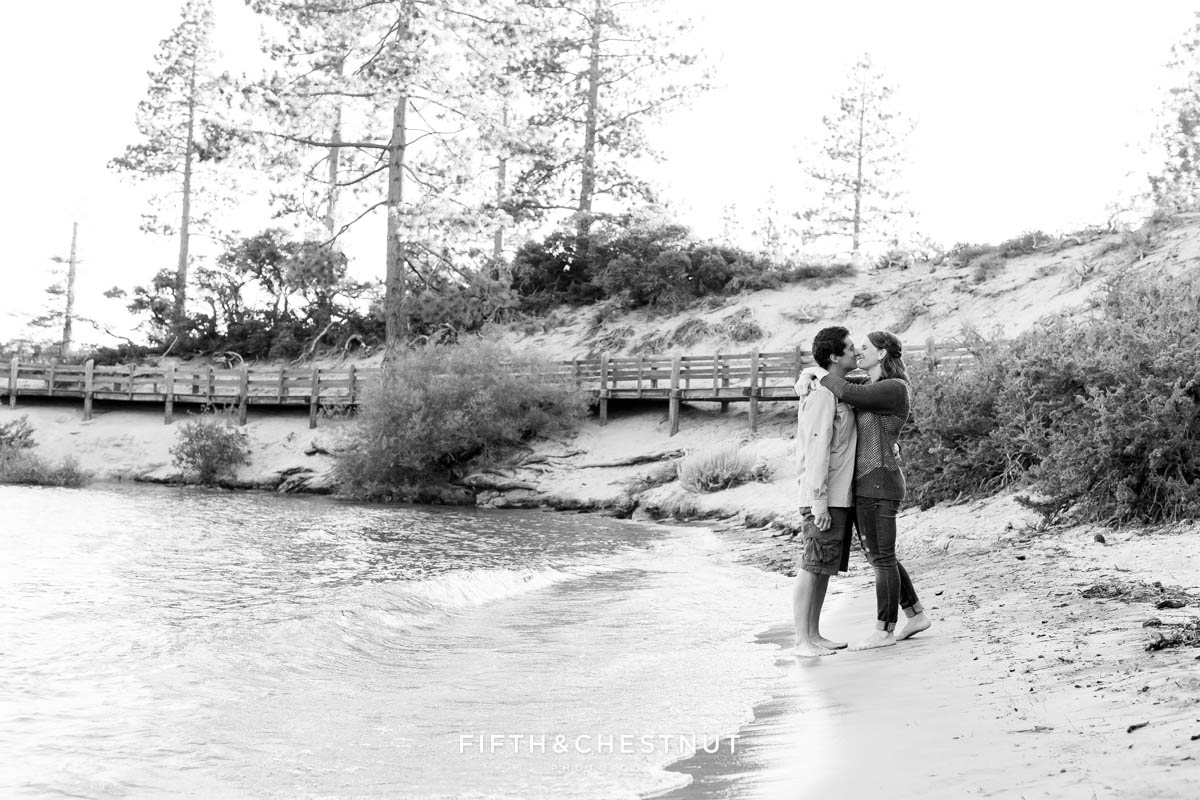 black and white image of couple kissing on the shore of lake tahoe at sand harbor